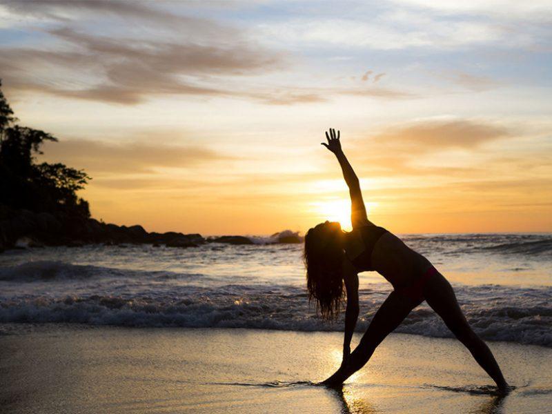 Yoga op het strand van Ibiza met zonsondergang